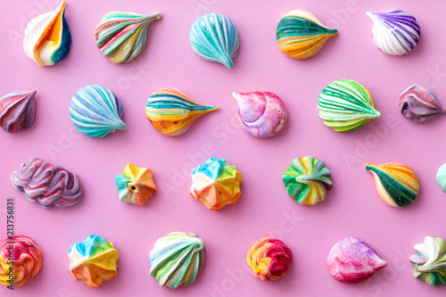 Colorful little meringue cakes on a pink pastel background. Appetizing meringues.