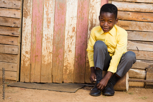 Canvas-taulu Black boy sitting down and tieing his shoes