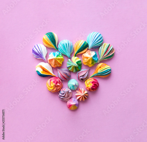 Colorful meringue cakes make a heart shape. The style of minimalism.