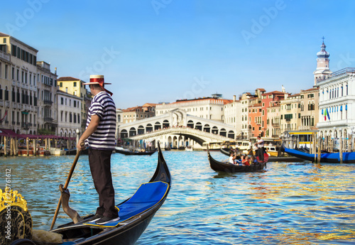 Poster Gondoles Venice, Italy. Gondolier with rowing oar in his gondola on Grand Canal look at Rialto Bridge against other gondolas in sunny day