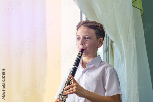 The boy learns to play the clarinet at the window Canvas Print