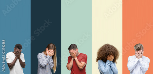Photo Group of people over vintage colors background with sad expression covering face with hands while crying