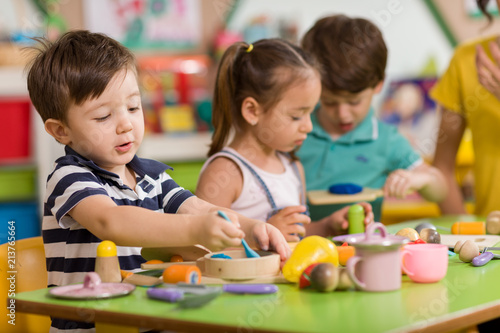 Fototapeta Childs are playing with play clay in classroom