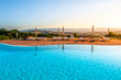 Beautiful luxury swimming pool with bright blue water, umbrellas and sunbeds in Tuscan landscape. Evening summer sunset. Italy.
