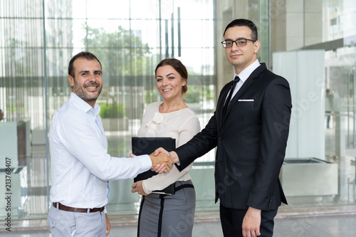 Fotomural Happy business people shaking hands and looking at camera
