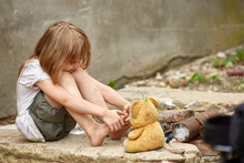 Orphan With Bare Feet In A Shabby Clothes Playing With Used Teddy Bear On The Street.