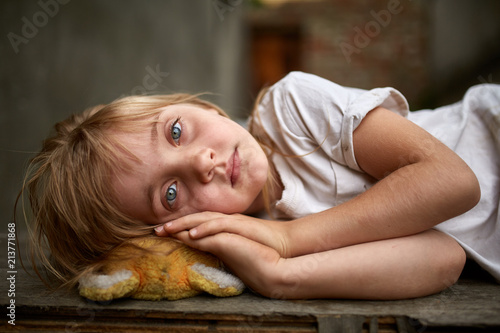 Fotografie, Obraz  Portrait of unfortunate stray kid lying on the board in the dirty alley, shallow depth of field