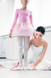 cropped shot of little african american ballerina exercising with teacher in ballet school