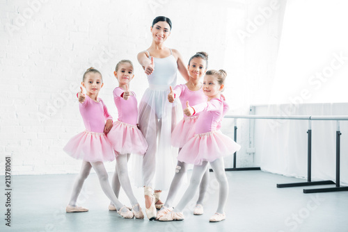 Fotografie, Tablou little ballerinas and ballet teacher showing thumbs up and smiling at camera in