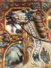 Head Shot Of Vintage Wooden Horse From Carousel Funfair Ride,with Painted Panels In Background