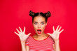 Closeup portrait of shocked girl with brown eyes and red lipstick on the mouse look at the camera with his fingers spread wide. Concept of advertising isolated on red background