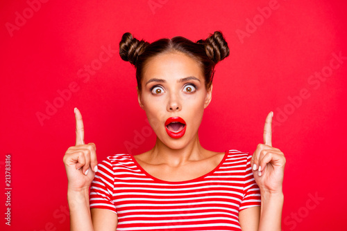 Photo Close up portrait of astonished girl with wide open mouth gesturing index fingers up isolated on red background