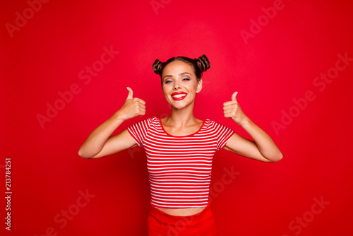 Fotografía  Young happy and cheerful woman showing thumb up by both hands isolated on red ba