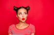canvas print picture - Attractive young girl with nice make up wearing striped tshirt puffed up her lips and looked up isolated on bright red background with copy space