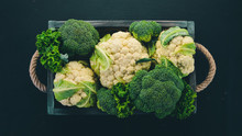 Cauliflower And Broccoli In A Wooden Box. Fresh Vegetables. On A Wooden Background. Top View. Copy Space.