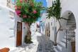 Traditionelle weiße Gasse mit bunten Oleander Blumen und farbigen Türen auf den Kykladen in Parikia, Paros, im Sommer, Griechenland