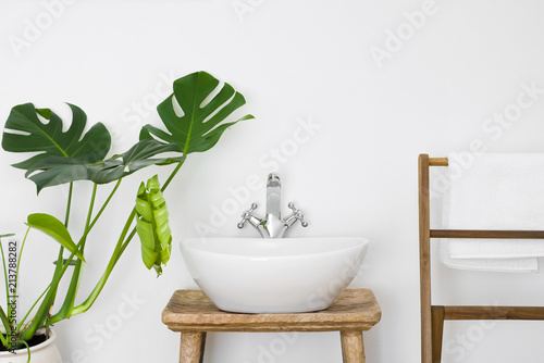 Fotografía Bathroom interior with white sink, towel hanger and green plant