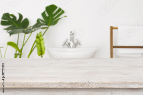 Fotografía  Wooden table top for product display over blurred bathroom interior