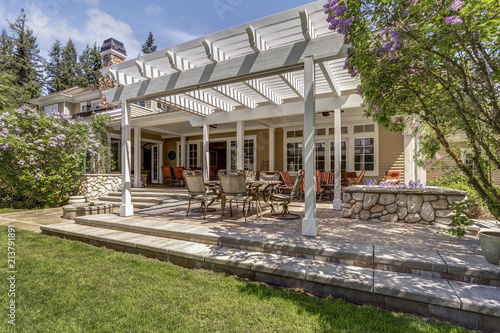 Fotografia  Lovely outdoor deck patio space with white dining pergola.