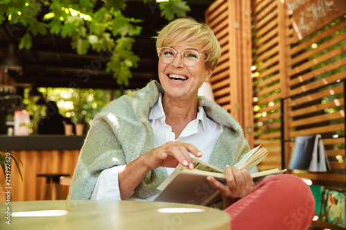 Fotografia  Happy mature woman wrapped in blanket reading a book