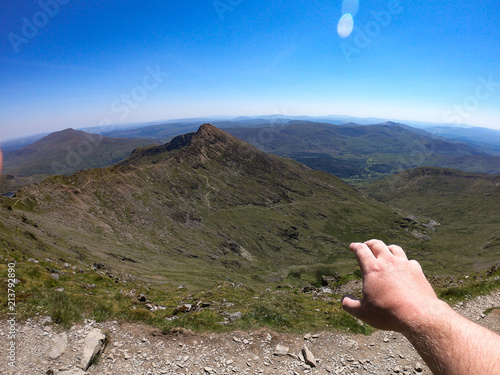 A hand reaches out over the views from Mount Snowdon, Wales, UK Fototapeta