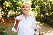 Cheerful Mature Woman Holding Green Apple