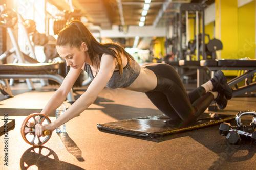 Cuadros en Lienzo Attractive slim sportswoman workout with abdominal roller in gym