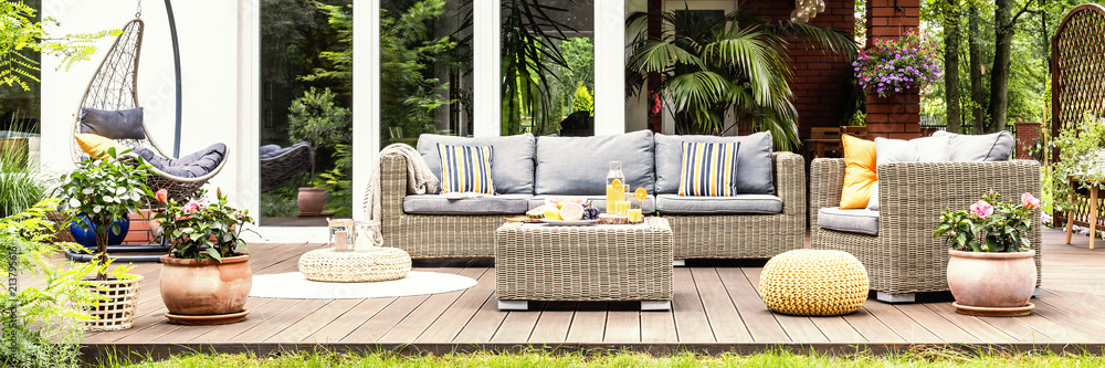 Fototapeta A relaxing spot for a warm, summer day - a stylish, wooden terrace with wicker garden furniture, cushions, plants and flowers