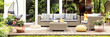 Leinwanddruck Bild - A relaxing spot for a warm, summer day - a stylish, wooden terrace with wicker garden furniture, cushions, plants and flowers