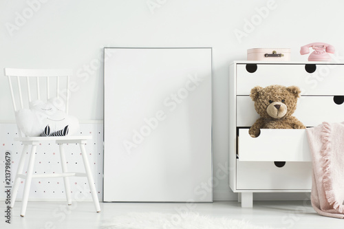Teddy bear and pink blanket in cabinet next to empty poster with mockup in baby's room interior. Real photo