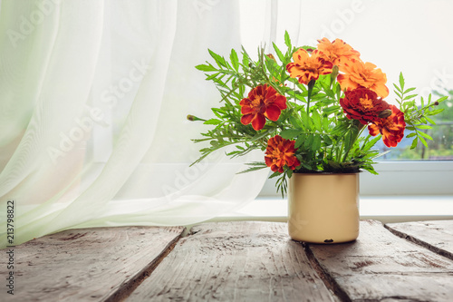 Stickers pour porte Fleur bouquet of orange flowers in an iron mug on the table near the window in a vintage style with a copy space