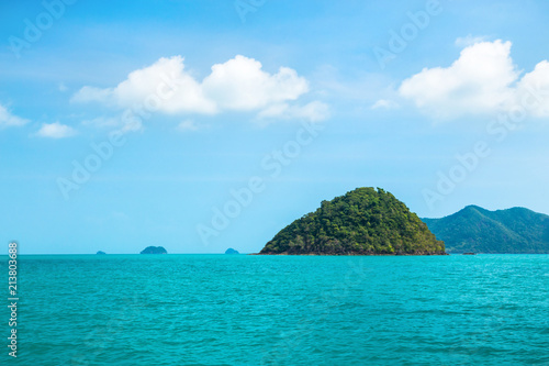 Spoed Foto op Canvas Eiland Small green island of pyramid shape in the tropical sea against a blue sky with white clouds. In the background mainland.