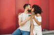 young multiethnic couple holding paper cups and kissing on street