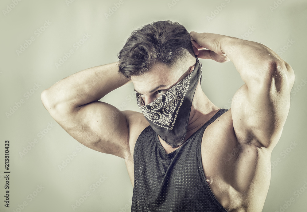 Fototapeta Handsome muscular young man with mask over face as a robber or bandit
