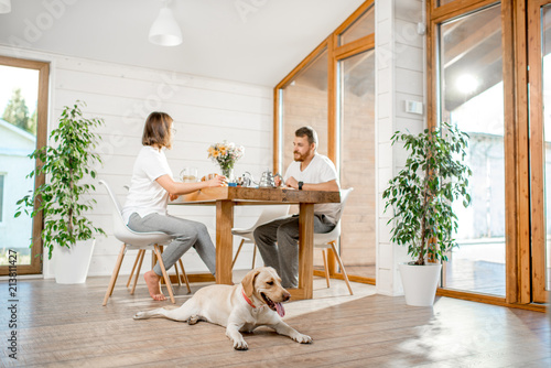 Fotografía  Young couple having a breakfast sitting with dog in the dining room in the woode
