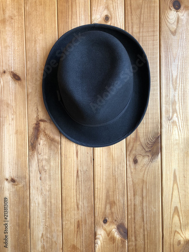 Poster de jardin Vache Black classic hat hanging on a wooden wall. Felt hat on a wooden background. Blogger attribute, fashion accessory.