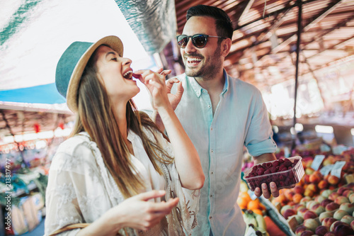 Young couple buying fruits and vegetables in a market on a sunny morning Poster Mural XXL