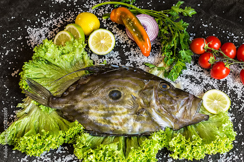 Photo  John Dory raw fish with tomatoes, lemon, salad, parsley, eat composition