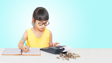 Little Girl Use Caculator And Note For Money.