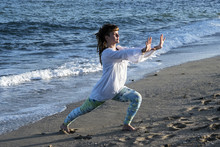 Young Woman With Brown Hair Wearing White Blouse Standing On A Beach By The Ocean, Doing Tai Chi.