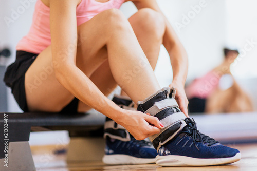 Woman at gym putting ankle weights Wallpaper Mural