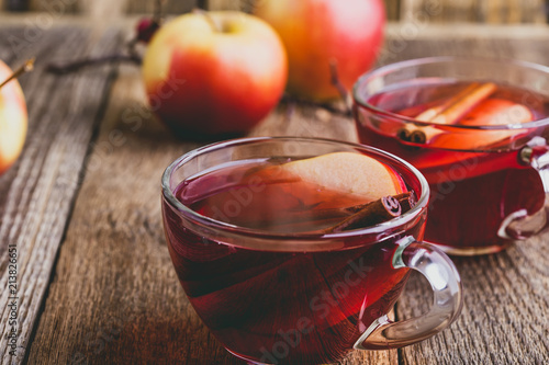 Hot drink with apple cider, sliced fruit and cinnamon stick