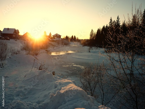 Foto op Aluminium Zwart Winter landscape. Snowy forest with background of small village and cold river at the sunset time