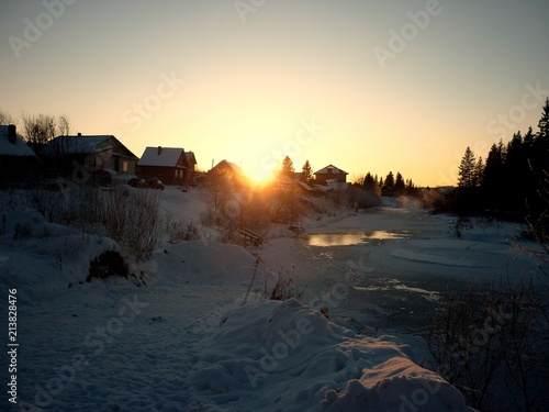 Staande foto Zwart Winter landscape. Snowy forest with background of small village and cold river at the sunset time