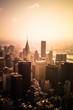 View of buildings across New York City skyline under golden sunset light