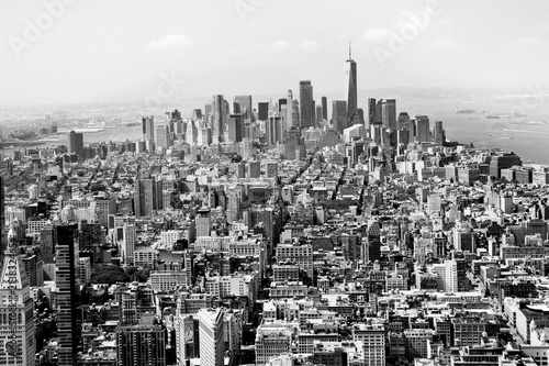 Cityscape skyline of various buildings, skyscrapers and architecture looking down on midtown Manhattan in New York City towards downtowns Financial District in black and white