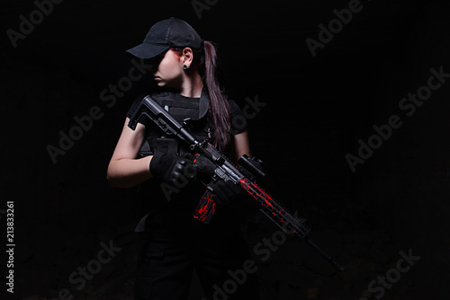 Fotografiet  Girl with rifle on dark background