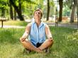 Beautiful mature woman meditating in green park