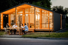 Backyard Of The Modern Wooden House Decorated With Lights With Friends Dining At The Table At The Evening