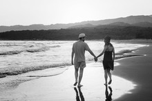 Young Lovely Couple Walking On Windy Coast Line. Back Horizontal View